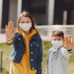 young-friends-with-medical-masks-on-street-4127435